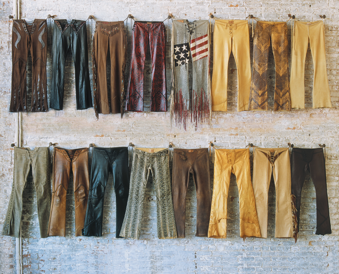 Hand-made Lost Art™ Custom Leather Pants with Leather fringe and Custom Details hanging on wall